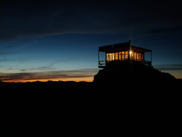 The sun sets over the horizon silhouetting a lookout tower with a single light glowing inside.